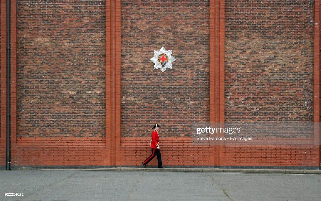 A soldier from the 1st Battalion Coldstream Guards walks past the regimental badge at Victoria Barracks in Windsor, Berkshire, in preparation for Trooping the Colour.