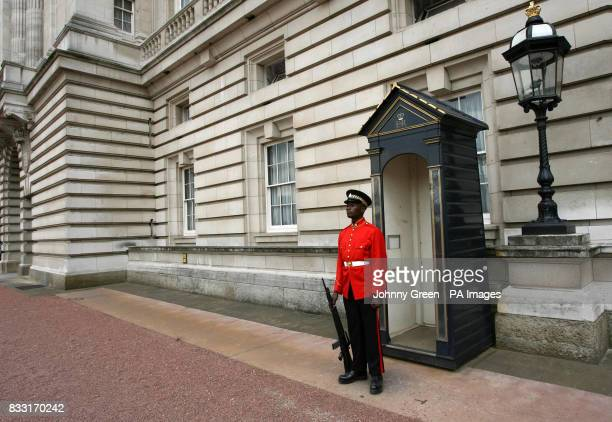 A soldier from the 1st Battalion Jamaican Regiment stands on guard by a sentry box at Buckingham Palace in central London following a parade during...