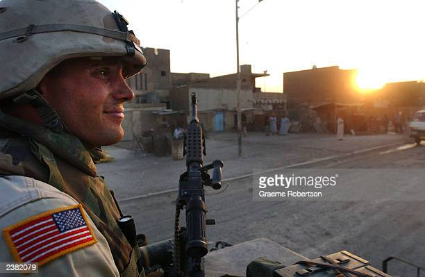Soldier from the 2nd Armored Cavalry Regiment mans the machine gun on top of a tank August 8, 2003 in Baghdad, Iraq. The 2nd ACR are patrolling...