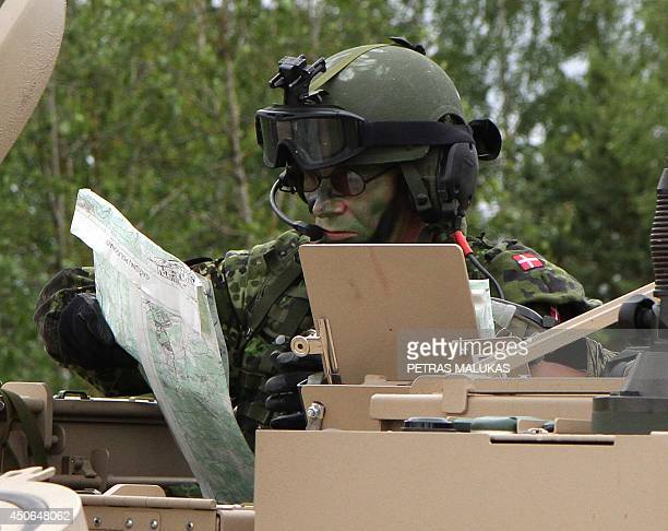 A soldier from the 2nd Brigade of the Danish Division looks at a map as he takes part in a field training exercise during the first phase Saber...