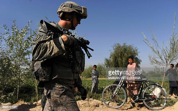 A US soldier from the 2nd Platoon Alpha 371 cavalry walks past a group of children on the roadside during a patrol mission in the Baraki Barak...