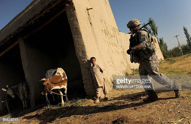 A US soldier from the 2nd Platoon Alpha 371 Cavalry walks past an Afghan child during a patrol mission at Sarbland villagein the Baraki Barak...