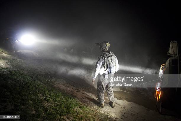 US soldier from the 3rd Brigade 10th Mountain Division assists in trying to recover a Humvee that became stuck in the mud during a night patrol May...