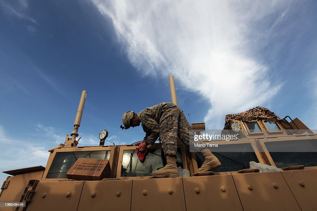 A soldier from the 3rd Brigade, 1st Cavalry Division cleans a Mine Resistant Ambush Protected (MRAP) vehicle while preparing to depart in the last convoy from Iraq at Camp Adder, now known as Imam Ali Base, on December 17, 2011 near Nasiriyah, Iraq. Around 500 troops from the 3rd Brigade, 1st Cavalry Division ended their presence on Camp Adder, the last remaining American base, and departed in the final American military convoy out of Iraq, arriving into Kuwait in the early morning hours of December 18, 2011. All U.S. troops were scheduled to have departed Iraq by December 31st, 2011. At least 4,485 U.S. military personnel died in service in Iraq. According to the Iraq Body Count, more than 100,000 Iraqi civilians have died from war-related violence.