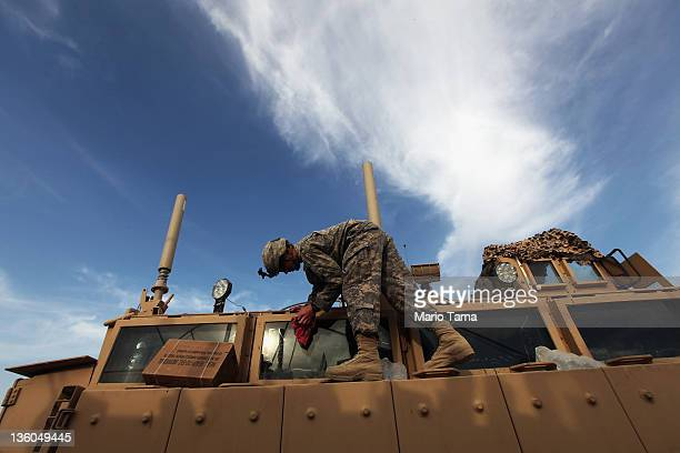 A soldier from the 3rd Brigade 1st Cavalry Division cleans a Mine Resistant Ambush Protected vehicle while preparing to depart in the last convoy...