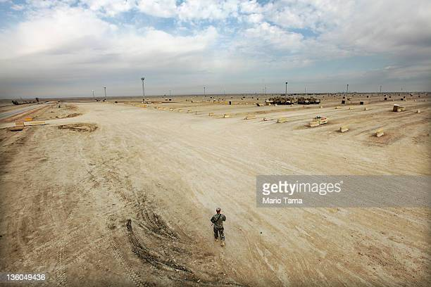Soldier from the 3rd Brigade, 1st Cavalry Division, walks through the nearly deserted Camp Adder, now known as Imam Ali Base, on December 16, 2011...
