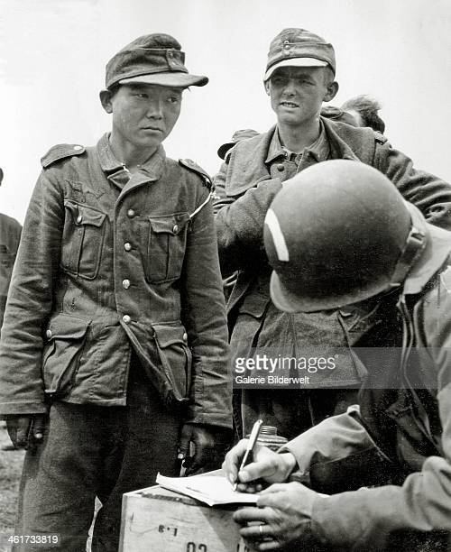 Soldier from the 5th Engineer Special Brigade ,with a white bow on the helmet, is registering the names of prisoners of the Wehrmacht. 7th June 1944....
