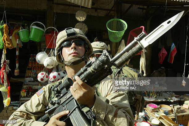 Soldier from the 82nd Airborne division stands on guard in a commercial street in Fallujah, during a search for a weapons cache in the area, 50 kms...