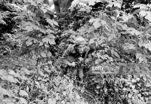 A soldier from the Atlacatl Battalion advances during a military operation pursuing guerrillas from the Farabundo Martí National Liberation Front in...
