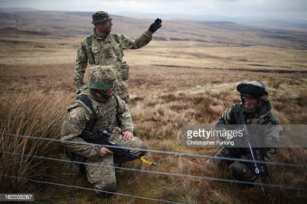 A soldier from the French Army guards an observation post with gunners from the Royal Artillery on February 20 2013 in Otterburn United Kingdom...