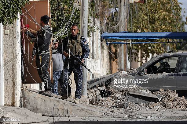 A soldier from the Iraqi Special Forces and policemen offer flowers to a resident of the Aden district of Mosul after troops almost entirely retook...