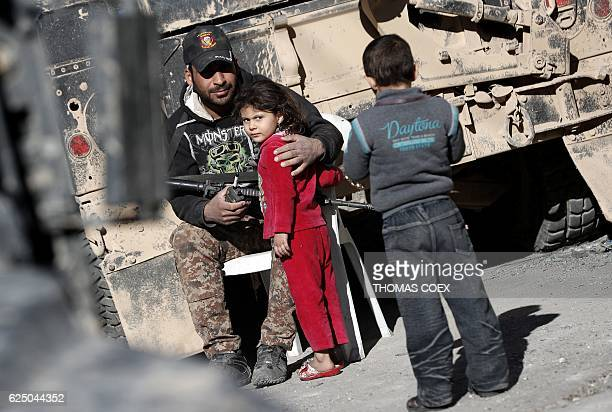 TOPSHOT A soldier from the Iraqi Special Forces hugs a girl living in the Aden district of Mosul after troops almost entirely retook the area from...