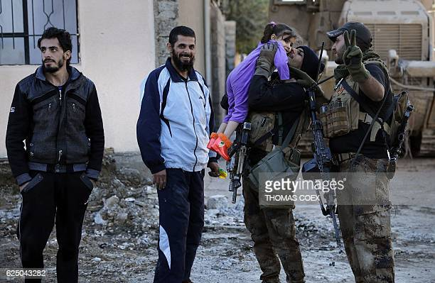 A soldier from the Iraqi Special Forces kisses a girl while patroling a street in the Aden district of Mosul after troops almost entirely retook the...