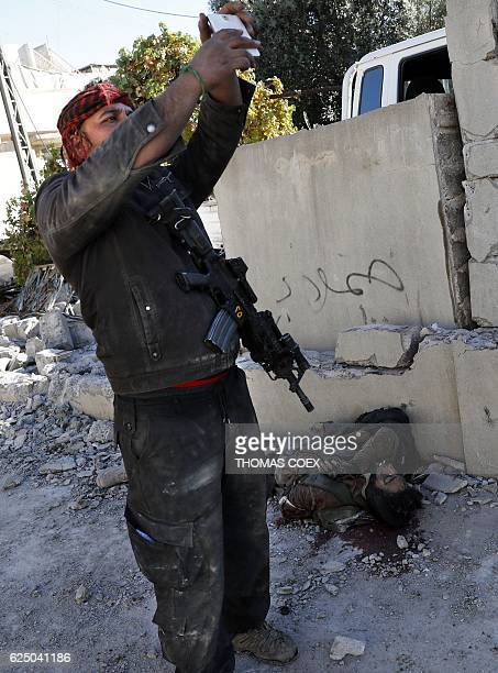 A soldier from the Iraqi Special Forces takes a selfie next to the body of a suspected Islamic State group fighter in the Aden district of Mosul...