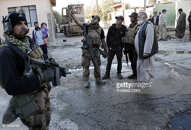 A soldier from the Iraqi Special Forces takes a selfie with residents of the Aden district of Mosul after troops almost entirely retook the area from...