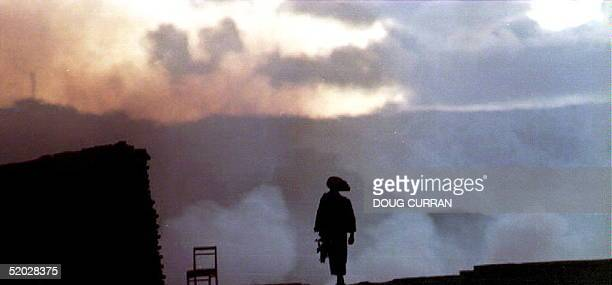 A soldier from the JamiatiIslami mujahedeen organization is silhouetted against rising smoke at twilight 18 May 1992 after a fire broke out at a...