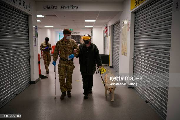 Soldier from The King's Royal Hussars, who normally crews a main battle tank, helps a visually impaired member of the public at a coronavirus Flow...