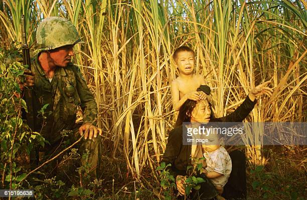 A soldier from the Korean White Horse Division on an offensive north of Bong Son kneels beside the bedraggled mother and children of a suspected...