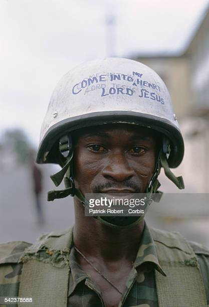 A soldier from the multinational West African peacekeeping forces of ECOMOG patrols the streets of Monrovia wearing a helmet that says Come into my...