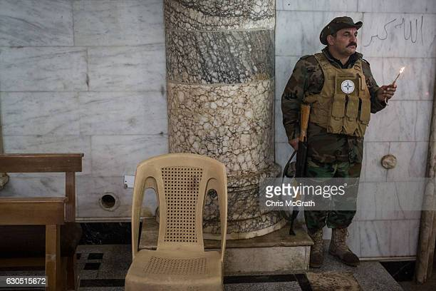 Soldier from the NPU holds a candle while attending Christmas Day mass at Mar Hanna church in Qaraqosh on December 25, 2016 in Mosul, Iraq. The...