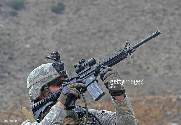 A US soldier from the Provincial Reconstruction team Steel Warriors looks through the scope of his assault rifle during a patrol in the mountains of...