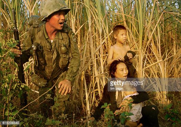A soldier from the Republic of Korea beside a Vietnamese family north of Bong Sen | Location north of Bong Sen Vietnam
