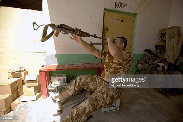 Soldier from the Romanian Army cleans his AK-47 weapon at Forward Operating Base Mizan in western Zabul Province, Afghanistan September 14, 2006. The...