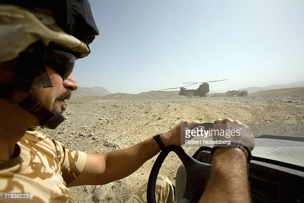 Soldier from the Romanian Army drives a 6-wheeled Gator to meet an incoming US Army CH-47 helicopter at Forward Operating Base Lane in Zabul...