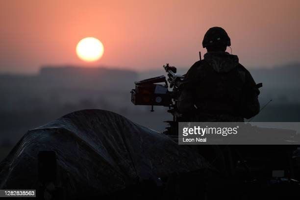 Soldier from the Royal Anglian Regiment guards the perimeter of the camp from a Coyote tactical support vehicle at sunrise during a Mission Rehearsal...