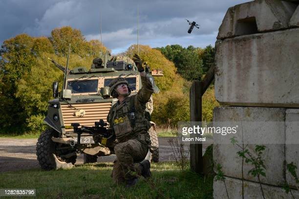 Soldier from the Royal Anglian Regiment launches a DefendTex D40 under-slung grenade launcher deployed drone during a Mission Rehearsal Exercise...