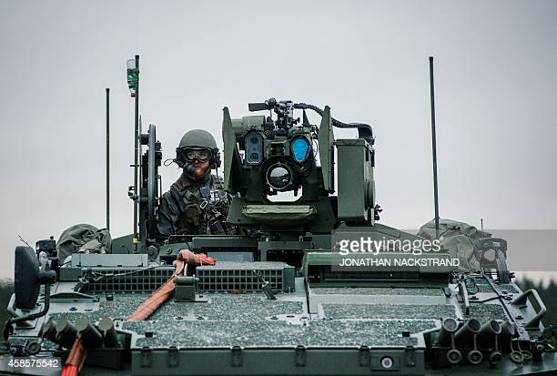 A soldier from the Swedish Armed Forces looks on from top of the Patria XA360 AMV at Hagshult Airbase part of the Forward Operation Base of the NBG...