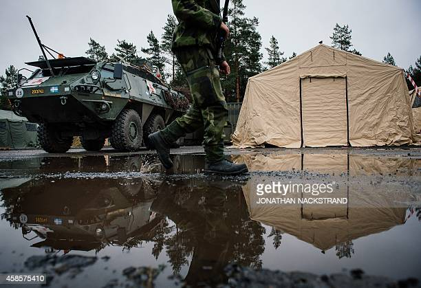 A soldier from the Swedish Armed Forces walks next to an Patria XA360 AMV Ambulance at a Motorised Infantry Battalion in Hagshult Airbase part of the...