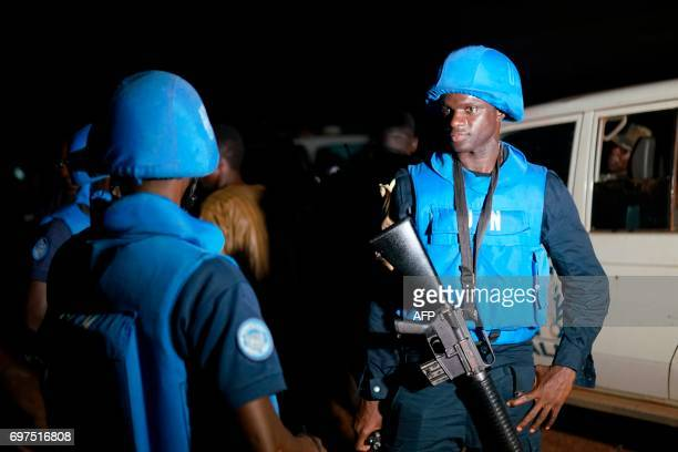 A soldier from the United Nations Multidimensional Integrated Stabilization Mission in Mali stands while Malian forces carry on clearing operation in...