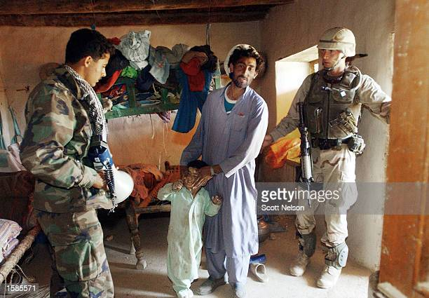 Soldier from the U.S. Army 82nd Airborne Division reunites an Afghan father and son after the small boy hid under a bed during a sweep of homes...