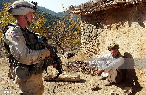 Soldier from the U.S. Army 82nd Airborne guards an Afghan elder as troops conduct a sweep of homes November 2, 2002 in the village of Naray in...