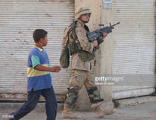 S Soldier from the US Army's1st Armored Division patrols the street June 23 2003 in the AlshekMaruf neighborhood of Baghdad Iraq About 900 soldiers...