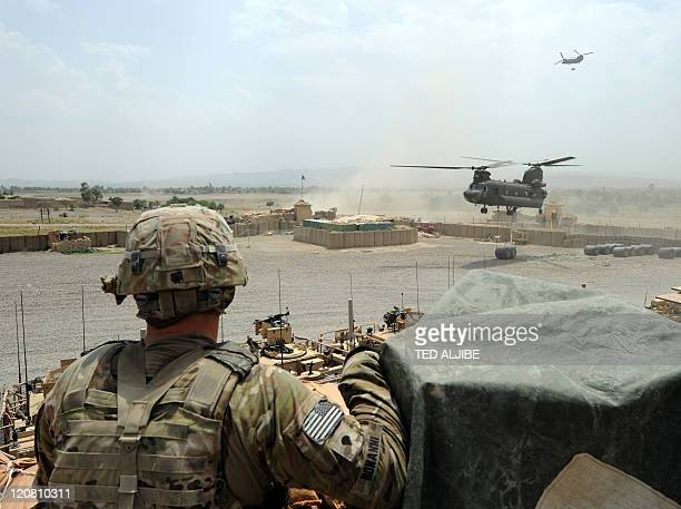 A US soldier from Viper Company 126 Infantry watches as US military Chinook helicopters unload fuel supplies at Combat Outpost Sabari in Khost...