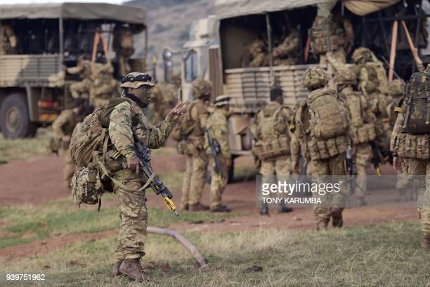 A soldier gestures as others climb a military vehicle during a simulated military excercise of the British Army Training Unit in Kenya together with...