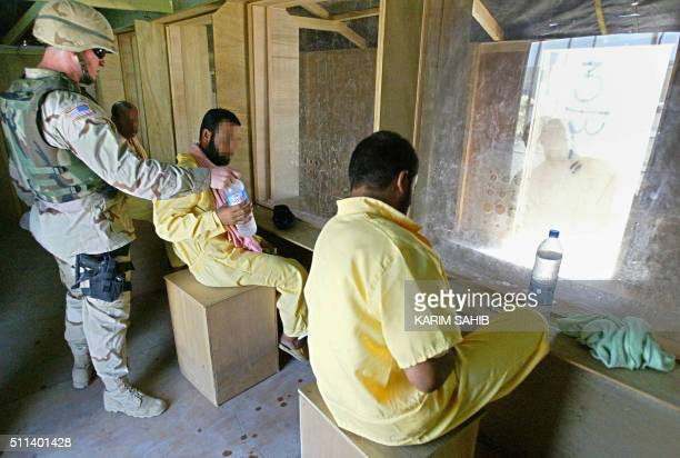 A US soldier gives a bottle of mineral to water to an Iraqi prisoner in yellow overall as he waits with other inmates in a cage at the Abu Ghraib...