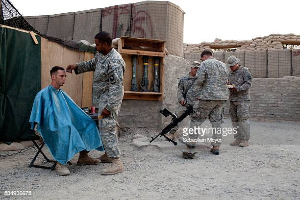 A soldier gives another soldier a haircut while others eat dinner Bravo 'Bonecrusher' Troop of the 175 Cavalry 101st Airborne Division recently...
