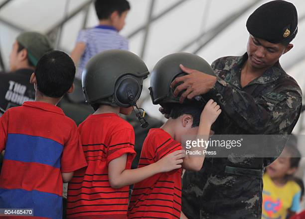 A soldier gives hat to a child during the National Children's Day at the Horse Brigade Bangkok Weapons such as tanks troop transport artillery guns...