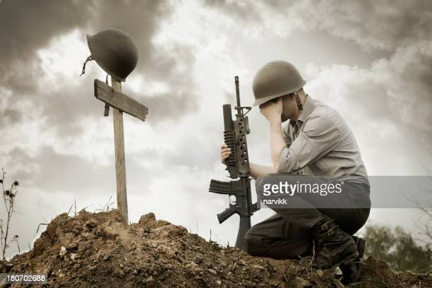 soldier grieving for dead friend - dead soldier stock photos and pictures
