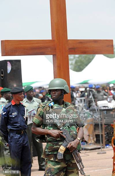 A soldier guarding the funeral of Nigeria secessionist leader Odumegwu Ojukwu stands before a cross during the national interdenominational funeral...