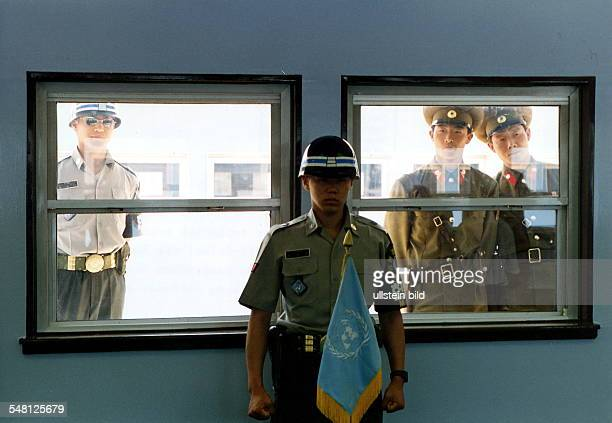 UN soldier guarding the shack where South and North Koreans meet for occasional talks a South Korean and two North Korean soldiers are looking...