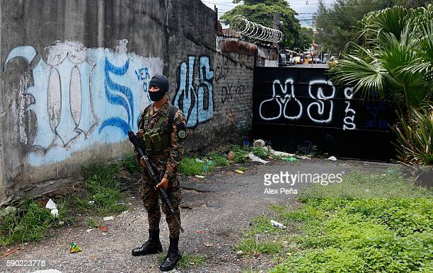 A soldier guards a graffitti area during a cleaning action of Gang graffitis on August 16 2016 in San Salvador El Salvador President of El Salvador...
