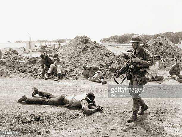 A US soldier guards bound Cuban and Grenadan prisoners at the Point Salines Airfield during the Grenada Invasion