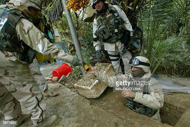 US soldier hands his comrade a camera at the hole where toppled dictator Saddam Hussein was captured in Ad Dawr near his home town of Tikrit 180 kms...