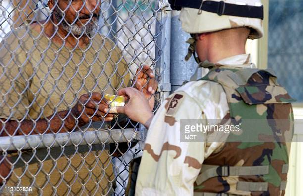 A US soldier hands out medicine to a detainee at Camp Bucca a USrun detention center in southern Iraq