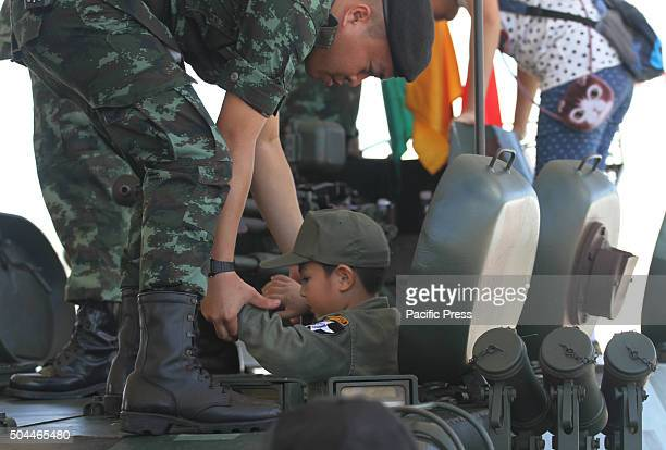 A soldier helps a child to sit on a tank during the National Children's Day at the Horse Brigade Bangkok Weapons such as tanks troop transport...