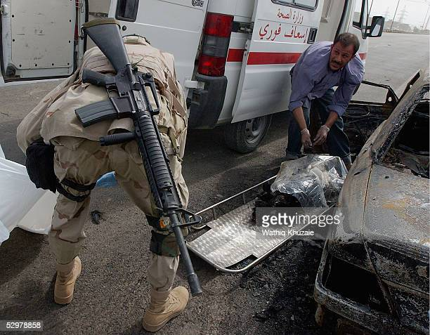 A US soldier helps an Iraqi paramedic as he removes a charred body at the scene of a suicide car bomb explosion which failed to hit a US military...